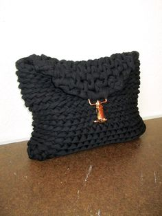 A black chunky knit clutch made of bulky t-shirt yarn.  Technically, this cuddly bag is not knitted but crocheted. Although it looks more like a knit. Its not lined and doesnt have any pockets - only one simple roomy compartment, but it makes the clutch reversible - just turn it inside out. See the last two photos to compare the 2 looks.  Choose the buckle color at checkout (shown with gold tone buckle).  MEASUREMENTS: Approximately 12 (19 cm) by 9 measured lying flat, not stretched.  NET…