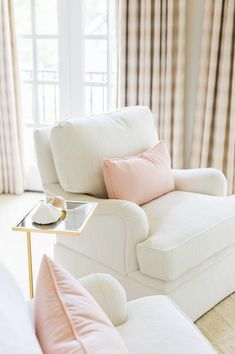 White and pink French bedroom sitting area boasts a pair of white roll arm chairs adorned with pale pink velvet pillows flanking a black and gold cigar table situated across from pink gingham curtains.