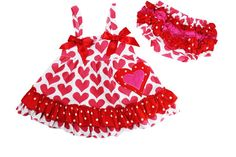 """The vintage heart swing top set for infant and toddler girls with red hearts and tons of adorable ruffles! The top is open in the back to show off the matching ruffled bloomers. Get our heart leg warmers for cool days and add a cute little sweater!     MONOGRAM/EMBROIDERY  If you would like your child's name or initial on the heart applique, please choose """"with monogram"""" then choose the size you need.     Please be sure to add the name or monogram initials to the note section of your order…"""