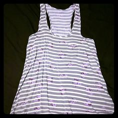 Racer back tank top Gray/white striped top with purple flowers. Small pocket on right side. Flowy. 100% Rayon. This top was bought at JCPenney, but I am not too sure on the exact brand. I did cut the tag out. Worn a few times, still in good condition. No holes, stains, etc. jcpenney Tops Tank Tops