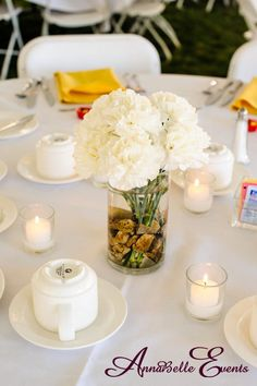 Chi Omega Sorority Centennial Event: glass cylinder vases with river rocks, white carnation flowers, and white floating candles. | AnnaBelle Events