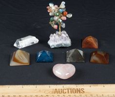 POLISHED PYRAMIDS IN DIFFERENT STONES. HEART SHAPED QUARTZ, CRYSTAL, AND A 4 IN HEALING STONE TREE WITH A GEODE ON BOTTOM.