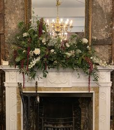 A lush meadow style mantle decoration including amaranthus, delphinium, roses, ammi and lots of lush foliage