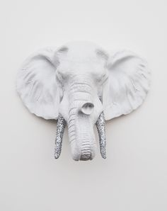 "WHITE RESIN ELEPHANT HEAD WALL ART W/SILVER TUSKS Measurements: • 20"" tall • 16.25"" wide • 10.5"" deep  Weight: • 12lbs • Each piece is cast out of a polyresin material, thus making the elephant sculpture fairly light in weight.  Hanging Instructions: • Use a monkey hook, strong nail or screw • The e..."