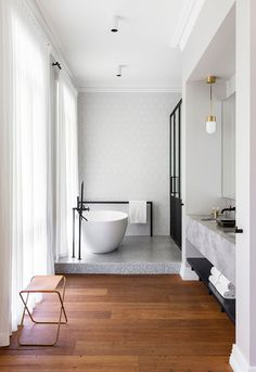 minimal bathroom, white tub black accents, leather stool, grey marble, wooden floors