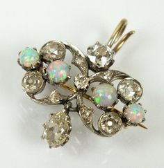 An early 20th century opal and diamond pendant/brooch, designed as a row of four round cabochon opals claw set within ten stone old cut diamond openwork mount, with pear shaped diamond set drop, all claw and collet set in white metal to yellow metal reverse, not stamped, presented within fitted Joseph Heming & Co box, 20mm wide x 20mm long, weight 4.1gms.