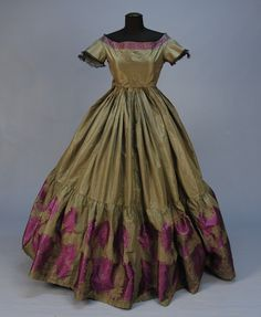 Civil War era fancy silk brocade evening gown. Green-grey taffeta 1-piece with short sleeve straight end bodice, the skirt having deep applied ruffle with elaborate purple and grey brocade floral, brocade and black lace trims the open neckline and sleeve, brown cotton bodice lining and hem band with braided trim. From a Salem, MA family.  Via Whitaker Auctions.