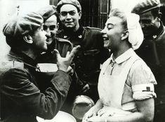 Cuatro soldados de la División Azul hablan con una enfermera de Cruz Roja en Grafenwöhr. soldados-Division-Azul-uniforme-aleman.j