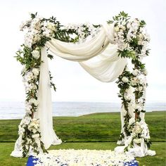 Romantic styling on an outdoor canopy - soft white draping and a variety of blooms