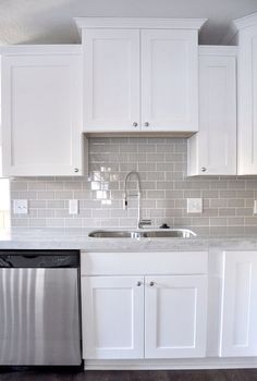 An example of gray subway tile in a white kitchen with white grout. Smoke Gray glass subway tile, white shaker cabinets, pull down faucet - gorgeous contemporary kitchen. Kitchen Cabinets Decor, Kitchen Redo, New Kitchen, Kitchen Dining, Copper Kitchen, Rustic Kitchen, Kitchen Storage, Awesome Kitchen, Kitchen Organization