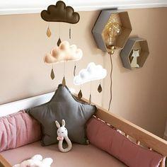 Un lit bébé en bois et un tour de lit couleur beige