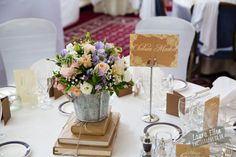 Bucket of flowers on pile of books. Surrey wedding flowers by Boutique Blooms floral design. Book Centrepiece Wedding, Pastel Wedding Centerpieces, Book Centerpieces, Centrepieces, Wedding Flowers, Table Decorations, Pile Of Books, Surrey, Fresh Flowers