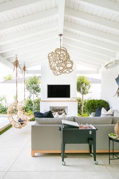 Beautiful outdoor living area - covered patio design idea with hanging chairs