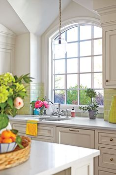 Green and orange accents help liven up classic white walls and cabinetry (painted Benjamin Moore's Ballet White) in this kitchen by designer Melissa Haynes.