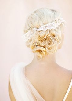 Yeah, the lace and plastic pearls are not so good, but I love the loose, vintage-y style, with the low hairpiece. By Gucio Photography via 100 Layer Cake.