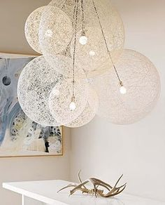 globe lights. Can totally make these from different size plastic balls and white yarn