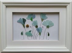 These naturally coloured sea glass flowers are set inside a 26cm x 35cm glazed box frame in either black or white.