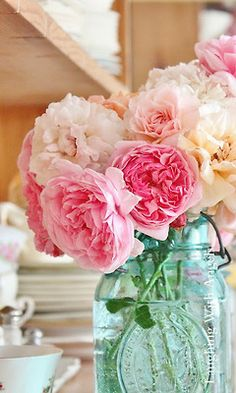 Pink camellias in a blue mason jar make a lovely shabby chic centrepiece.