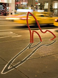 In 2008, David Byrne partnered with the NYC Department of Transportation on a series of wild bicycle racks. A spot near Bergdorf Goodman got the high heel rack, while Wall Street got the dollar sign rack. Later, shadows were added to the pavement by a NYC artist, amplifying the effect of these artistic pieces of infrastructure.