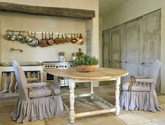 Stunning French Country kitchen designed by Pamela Pierce with antique table, slipcovered chairs,, rustic beam over range, and copper pots.