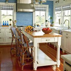 Light blue subway tile, butcher block-topped island, and beaded-board cabinet fronts lend plenty of cottage style to this Fire Island kitchen.