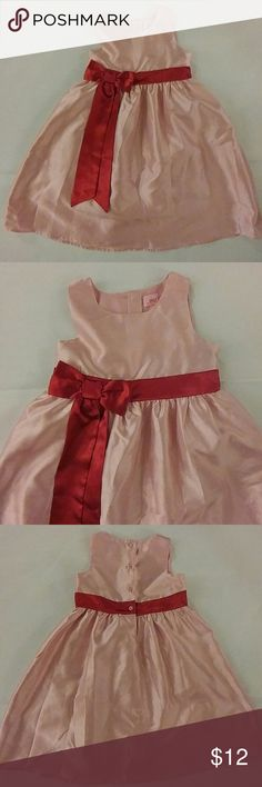 """Girl's pink party dress with red sash Perfect for the upcoming holiday season! This is a 100% polyester (slubbed to look like silk) pink sleeveless party dress with a lovely bright red sash and bow at waist. Fully lined. 4 button closure at back. Pleated full skirt falls 19"""" from bottom of waist sash. In excellent used condition (no visible stains, rips, or tears.) Our Generations Dresses Formal"""