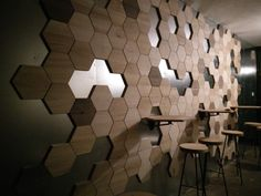 Hexagon tiles made of 6 different types of wood attached to the wall with neodymium magnets. Coffee place at SAFKO, Bratislava.