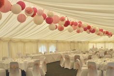 Lanterns, pom poms and honeycomb balls in shades of pink and ivory in a clustered line at Uplands House marquee.