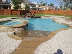 Gunite swimming pool with raised spa, beach entry, moss rock waterfall and flagstone coping.