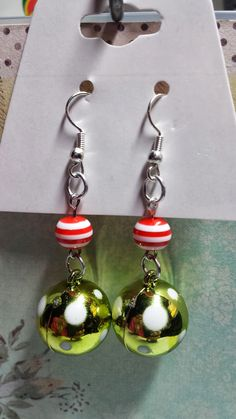 These adorable earrings are handmade by me. They each feature a round green bead with white spots and a red and white striped round bead.  $4