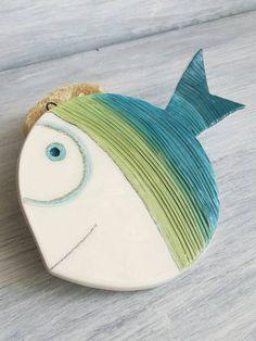 Ho disegnato ed intagliato questo pesce su lastra di argilla bianca, ho creato le incisioni decorative e lho rifinito con cura prima di procedere alla prima cottura a 970° per circa 10 ore. Successivamente lho dipinto pensando alle sfumature del mare, lho quindi immerso nella cristallina