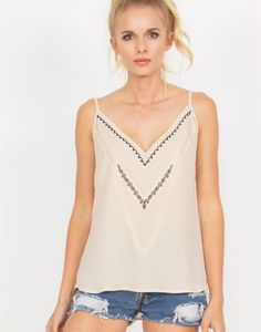 Nude cami top with embroidered details in the front. Adjustable straps.