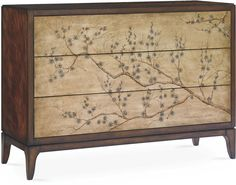 A stunning centerpiece for the master bedroom, this chinoiserie-inspired dresser shows off prized mahogany veneers and three sliding drawers with hand-painted cherry blossoms and gleaming gold-leaf panels. An alder frame sets a sturdy foundation, trimmed with a recessed bracket base and tapered legs. Furniture > Displays, Cabinets & Storage > Dressers.