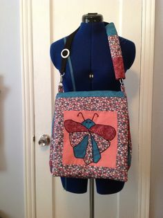 IPad purse, Kindle handbag, I Pad shoulder bag-One of a kind! This bag is quilted , cotton material,  applique butterfly with embroidery around it with beads for the eyes etc.  This bag has three pockets , two small pockets can hold cellphone and a large pocket.  Material is flower print, solid pink, teal and burgundy print.
