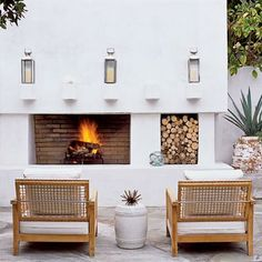 A simple outdoor fireplace makes a patio or porch functional year-round. Plush cushions on comfy wide-backed chairs make it the perfect place for enjoying a cocktail on a cool evening. coastalliving.com