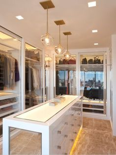 Boutique closet with sliding glass doors & mirrored island.