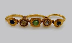 Gold triple-finger ring | Roman, Syrian | Late Imperial or Late Antique | The Met. This ring exemplifies a flamboyant type of costume jewelry that was especially popular in the eastern half of the Roman Empire. The three finger bands support five colorful settings, containing pearls, glass imitation gems, and a central green bead (a modern replacement).