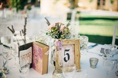 Romantic DIY decor including framed table numbers dropped in pearls and antique books as menus - An Allure Bridal gown for a wedding at the Fairytale Chateau in the Dordogne France with planning by Marry Me I France. The groom wears Cad and the Dandy and the maids wear twobirds bridesmaid dresses.