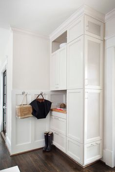 """The kitchen needed a """"touch-down"""" area for depositing book bags, bills and keys. This home organization center in the corner features a coat closet built into the side."""
