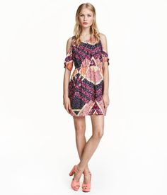 Short dress in crêped viscose with short raglan sleeves and cut-out sections at shoulders. Opening at back of neck with button, elasticized waist, and flared skirt. Unlined.