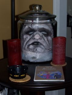 Head in a jar. Great thing to do with extra masks.  DIY decoration for front porch, party or decorating inside the home. Recycle your mask from costume to prop.