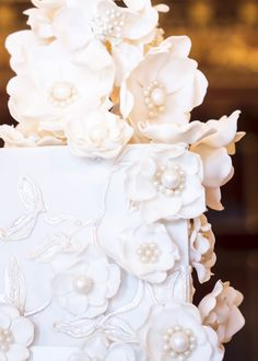 Detail of Rosalind Miller's Champagne Open Roses wedding cake covered with pearlised piping and elegant open sugar roses in champagne and ivory.