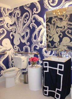 Lily Pulitzer - Fun bathroom with graphic blue and white octopus print wallpaper framing a navy and white greek key skirted sink below a backlit vanity mirror with a round white garden stool beside the toilet over white penny tiled floors. Penny Tile Floors, Tiled Floors, Bathroom Wallpaper Fish, Fish Wallpaper, Deco Cool, Deco Nature, Art Deco, Amazing Bathrooms, Decoration