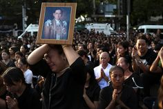 A woman cries while holding up a portrait of Thailand's King Bhumibol Adulyadej while his body is being moved from the Bangkok hospital where he died to the Grand Palace, in Bangkok, Thailand, October 14, 2016. REUTERS/Athit Perawongmetha