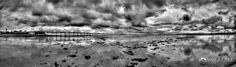 A dramatic black and white photograph of the Ocean Beach Pier in San Diego, CA at low tide.  The sweeping panoramic offers a 180 degree view with La Jolla, CA visible in the background.