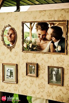 A photo booth wall with an old-fashioned look: wallpaper, detailed frames and vintage photographs.