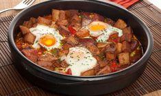 Receta de Bruno Oteiza de huevos a la flamenca, un plato elaborado con guisantes, patatas fritas en cubos, jamón, chorizo, pimiento rojo, salsa de tomate y huevos.
