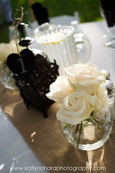 white roses in the gold mason jars with the mauve candles encircling each centerpiece. Keeps the mauve touches toned down