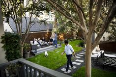Shown is the view from Michael Moore's and Chad Rothman's deck, looking toward the three new zones of their narrow backyard: an outdoor living room set on a raised platform, left; a strip of lawn, enjoyed here by the couple's dog, Jackson; and a fire pit, bar and movie screening area at right, partially out of frame.