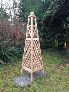"""Red Cedar Obelisk combining Trellis and Criss Cross design elements into a tall elegant structure. Obelisk is capped with 4 1/2"""" sphere finial."""